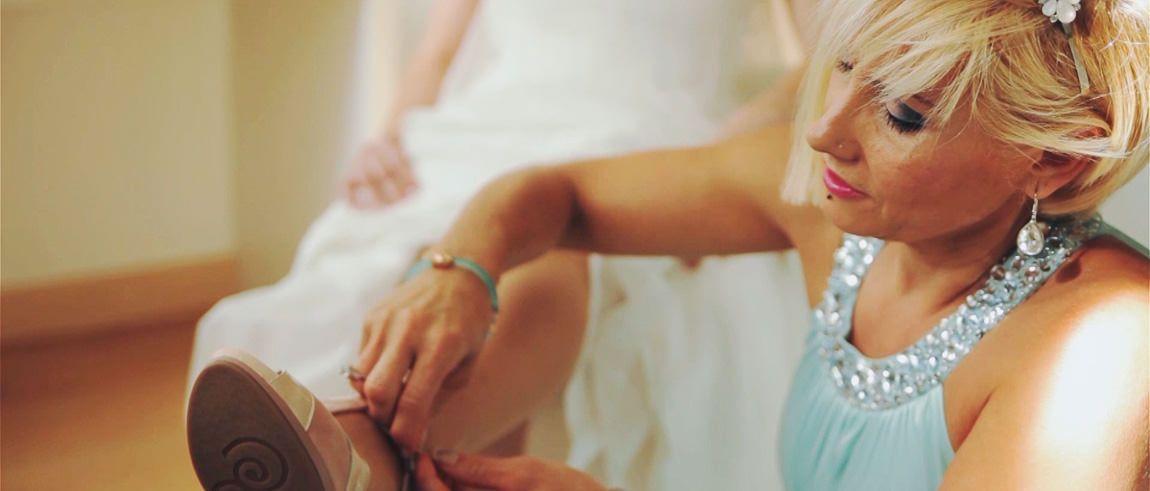 Una madre ayuda a una novia poner zapatos de boda